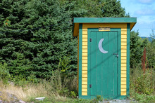 Yellow Outhouse With Green Trim And Green Door. There's A White Half Moon Painted On The Exterior Of The Door.  A Sign Hangs Over The Door With The Word Outhouse. Green Trees Are In The Background.