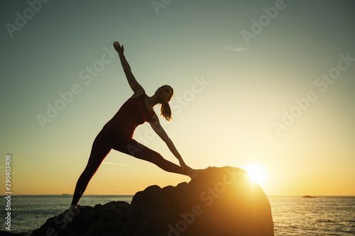 Spoed Foto op Canvas School de yoga Woman silhouette doing yoga exercise on sea beach during surreal sunset.