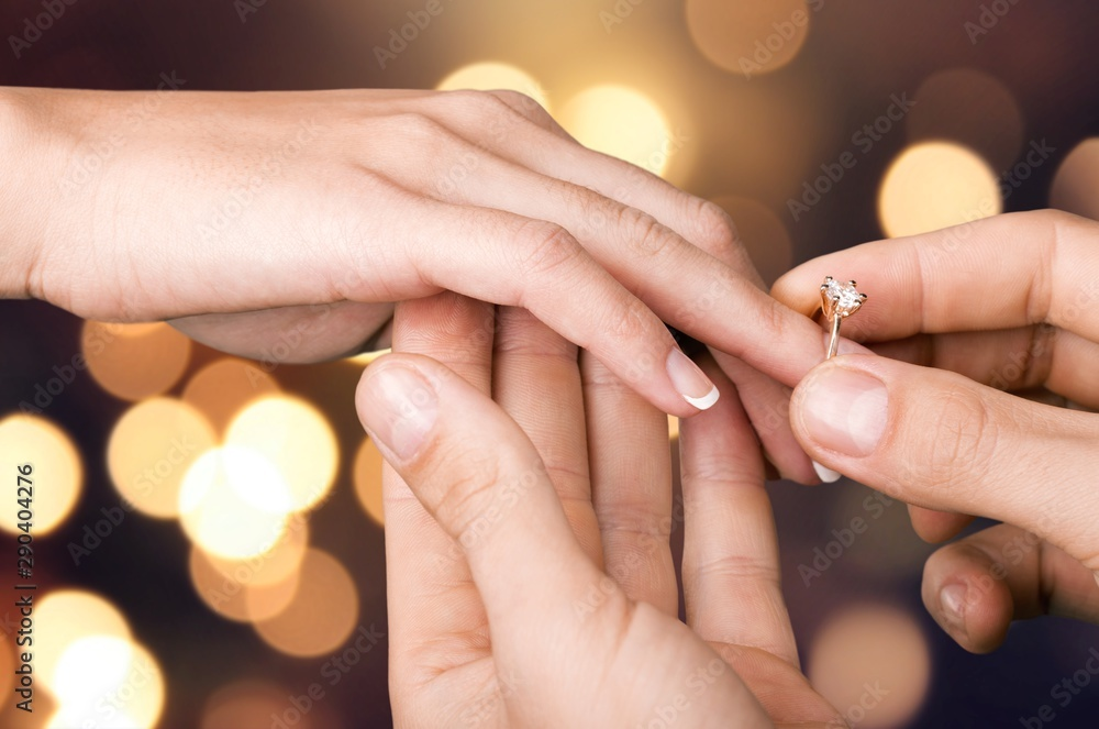 Fototapeta Close up Groom Putting the Wedding Ring on bride