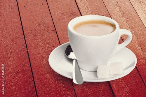 Cup of coffee and scattered coffee beans on wooden background