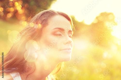 Foto auf Leinwand Logo Young woman on field under sunset light