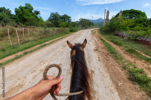 Horseback Riding on a dirty trail in the country side near a small Cuban Town during a vibrant sunny day Canvas Print