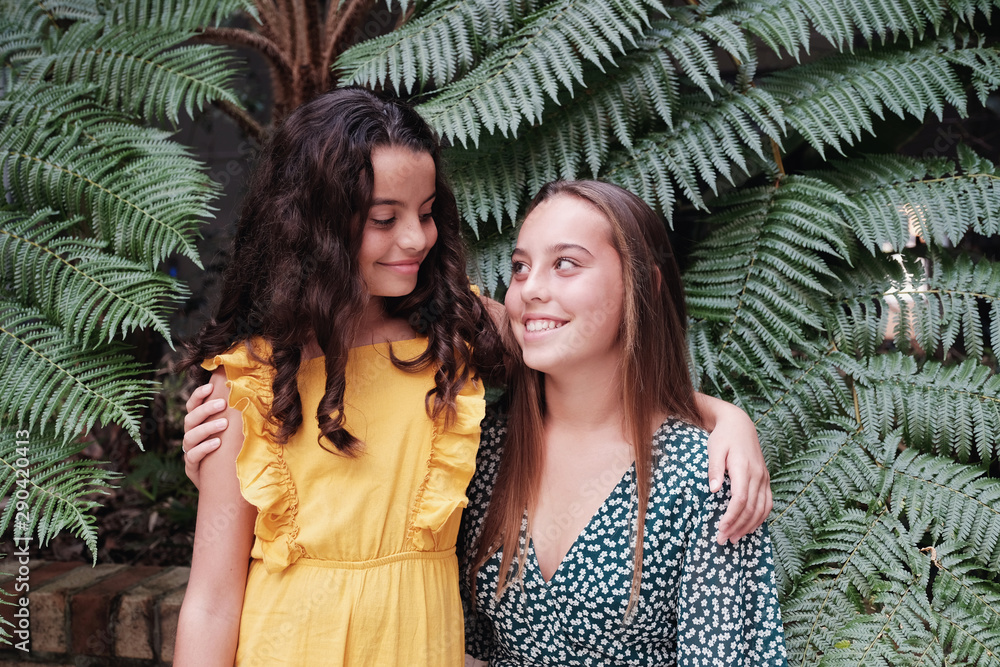Fototapety, obrazy: Mixed race family, beautiful preteen and teen sisters hugging and smiling at each other over grean tropical leaves, diversity people