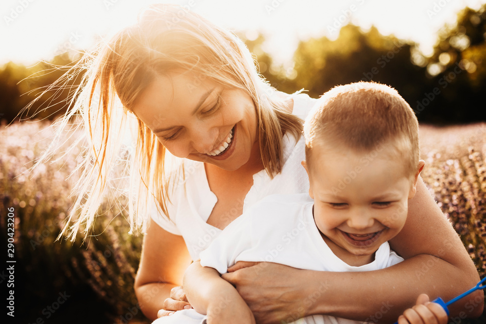 Fototapeta Beautiful young mother playing with her son outdoor against sunset. Woman tickling little boy outside. Sweet small kid laughing while embracing mother.