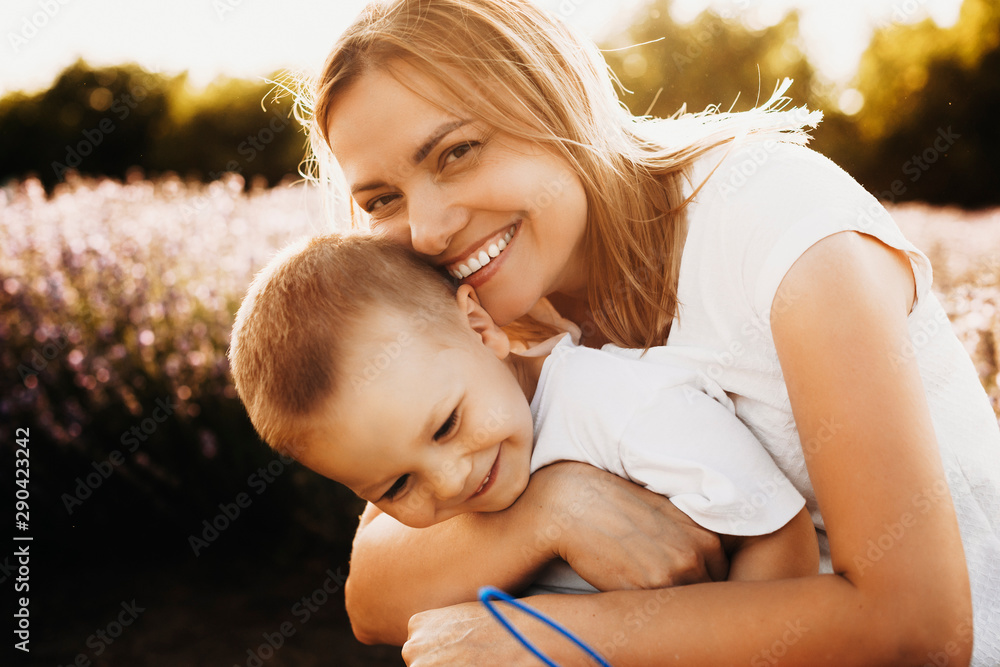 Fototapeta Close up portrait of a lovely young mother embracing his son outside against sunset. Young woman looking at camera laughing while playing with her little kid.