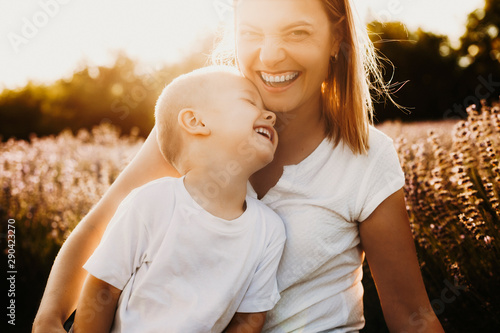 Fototapeta  Close up portrait of a sweet little kid laughing while embracing his mother