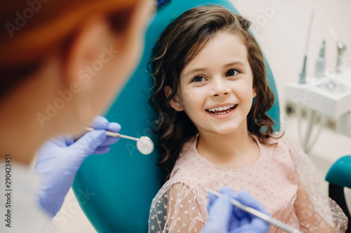 Lovely little kid smiling while talking with the pediatric dentist after doing a tenth examination in a pediatric stomatology.