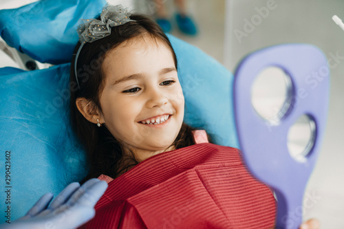 Fotografia  Happy little kid looking in the mirror after teeth examination in a pediatric stomatology