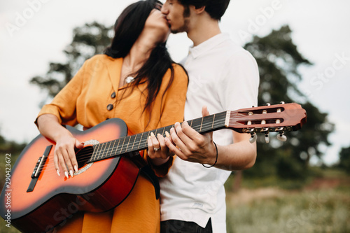 Obraz na plátně  Hands of a young couple holding a guitar while kissing outside in nature