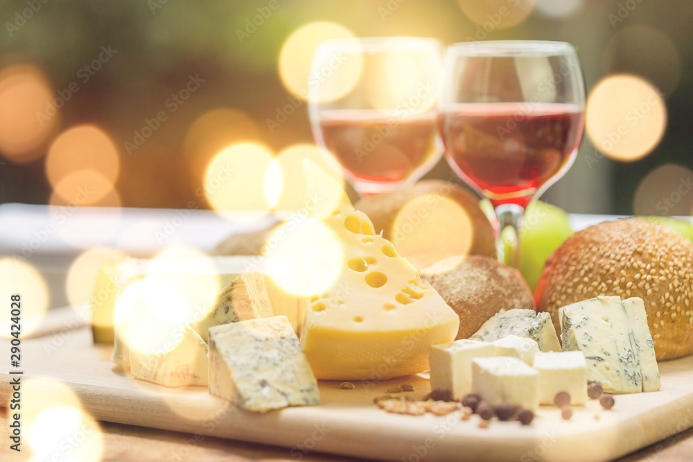 Fototapeta Assortment of cheese on board and two glasses of wine