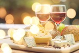 Assortment of cheese on board and two glasses of wine