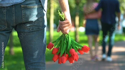 Fotografía Guy with tulips bouquet watching his girlfriend walking with another man