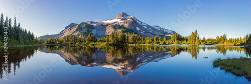 Volcanic mountain in morning light reflected in calm waters of lake.	 - 290425443