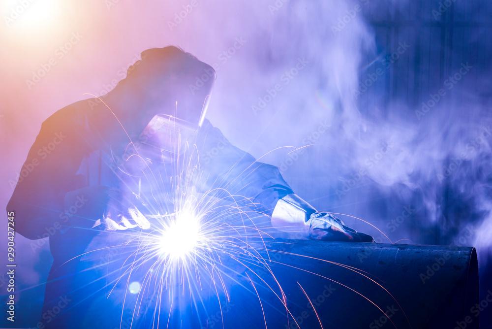 Fototapeta Industrial welders, industrial steel pipe parts, welding workers, steel workpieces