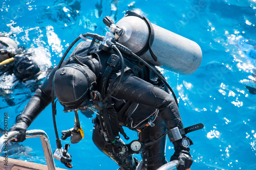 An unrecognizable woman in a wetsuit with a scuba gear rises to the deck of a yacht from blue sea water after diving Wallpaper Mural