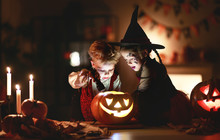 Happy Children In Costumes Of Witch And Vampire In A Dark House In Halloween.
