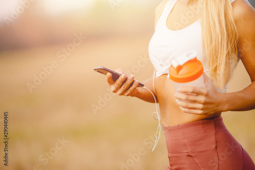Girl uses phone for online training with connected headphones, in hand sports bottle for water - 290440445