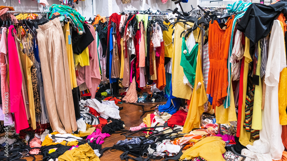 Fototapeta Messy clearance section in a clothing store, with colorful garments on racks and on the floor