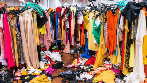 Fényképezés Messy clearance section in a clothing store, with colorful garments on racks and