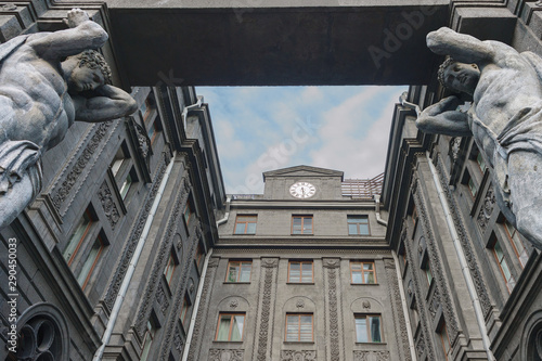 Photo Sculptures of Atlantes in the arch of the apartment building in St