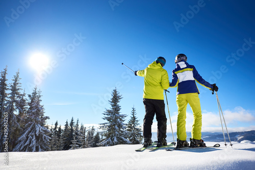 Cuadros en Lienzo  Male skier showing with ski poles on sun high in blue sky over winter mountains