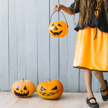 Girl In Black And Orange Dress Standing And Holding Halloween Basket