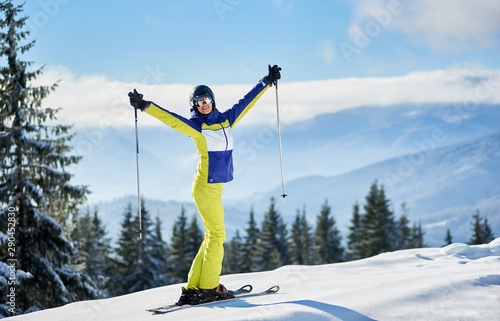 Fotografía  Smiling young woman in goggles posing on skis with hands up with ski poles on winter sunny day