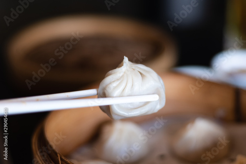Fotografía  Close up white chopsticks holding dim sum Ha gow over wooden basket