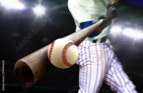 Baseball player hitting ball with bat in close up under stadium spotlights Wallpaper Mural
