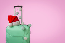 Plastic Suitcase, Santa Claus Cap And Garland On A Pink Background. Concept Of Travel, Business Trips, Trips To Visit Friends And Relatives On Christmas Holidays. New Year's Journey