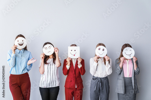Fotografía  Group of woman covering their faces with drawn emoticons against light backgroun