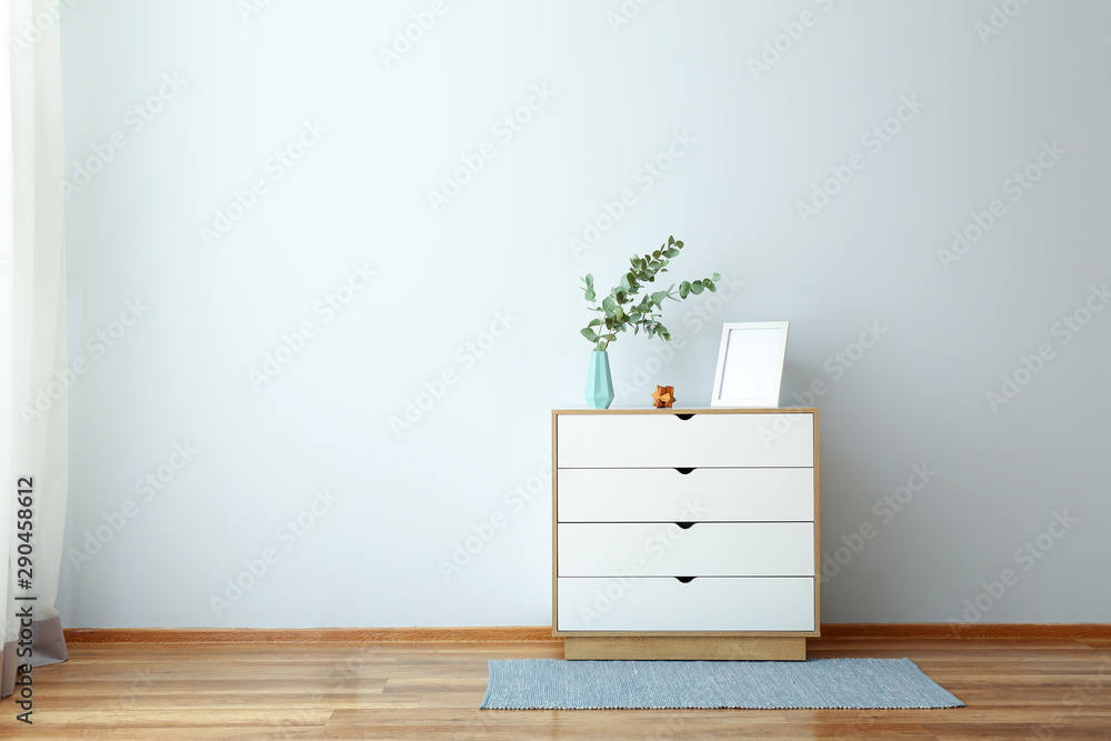 Fototapety, obrazy: Chest of drawers with eucalyptus branches in vase near light wall