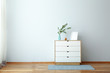 canvas print picture Chest of drawers with eucalyptus branches in vase near light wall