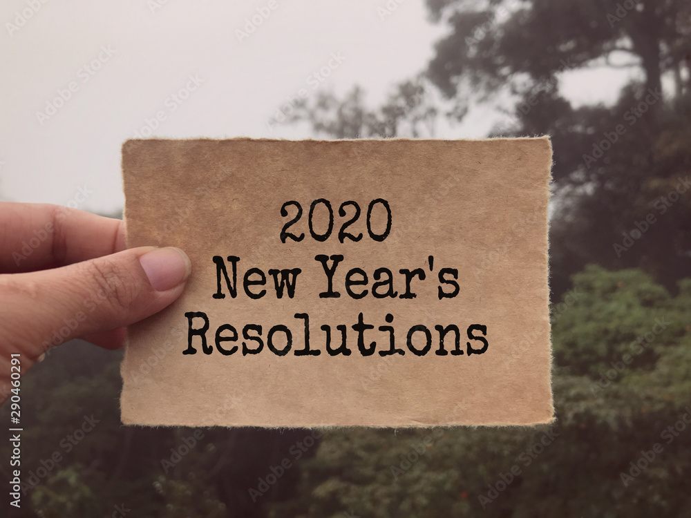 Fototapeta New year resolutions concept - 2020 New Year's Resolutions written on a paper. Blurred styled background.