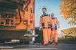 canvas print picture - Two refuse collection workers loading garbage into waste truck