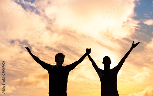 Photo  Silhouette of man and woman together with hands raised