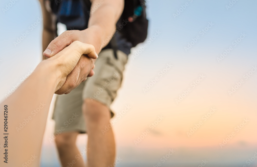 Fototapety, obrazy: Hikers climbing mountain, helping, giving hand to friend.