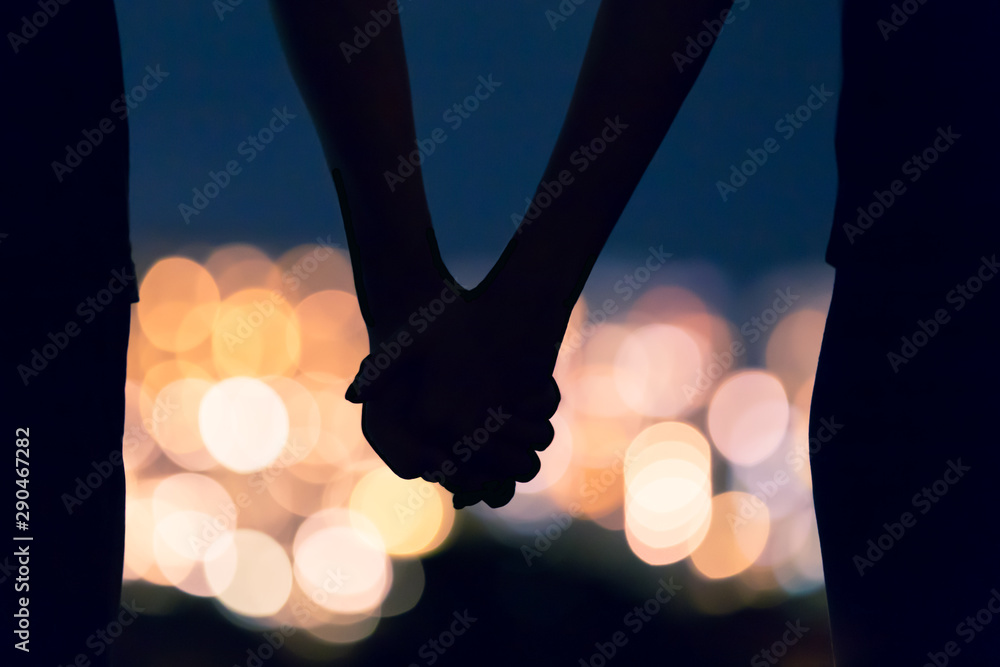 Fototapeta Couple holding hands facing city night lights.