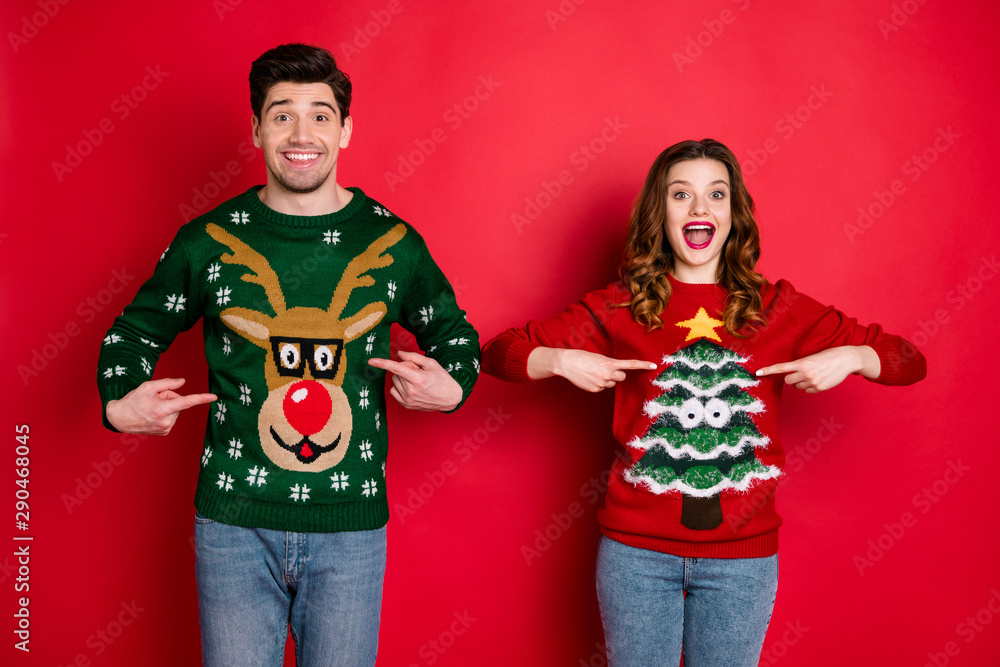 Fototapeta Midnight presents. Portrait of two brunet hair lovers people scream wow omg point indexf inger his her reindeer christmas tree pattern pullovers wear jeans isolated over red color background