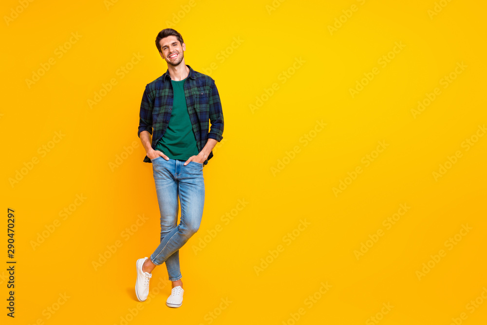 Fototapeta Full length body size photo of cheerful charming cute handsome man posing in front of camera with hands in pockets isolated over vivid color background