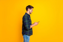 Profile Photo Of Blogger Guy Holding Telephone In Hands Checking Instagram Followers Wear Casual Plaid Shirt Isolated Yellow Color Background