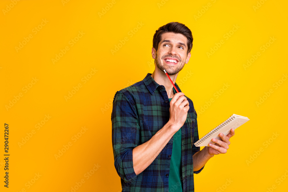 Fototapety, obrazy: Photo of nice guy with organizer in hands making notes creating startup idea wear casual checkered shirt isolated yellow color background