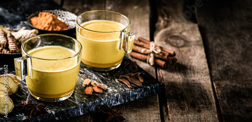 Cadres-photo bureau The Turmeric golden milk and ingredients on wood background, copy space
