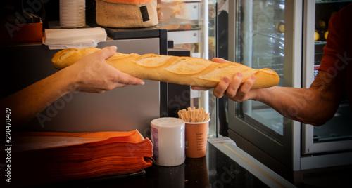 Commerçant boulanger artisan - cliente achetant une baguette de pain fraîche dan Canvas Print