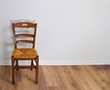 canvas print picture - Single vintage wooden chair in front standing alone on wooden floor in empty room. Large copy space for text.