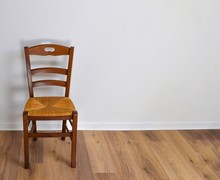 Single Vintage Wooden Chair In Front Standing Alone On Wooden Floor In Empty Room. Large Copy Space For Text.