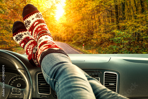 Photo sur Toile Amsterdam Woman legs with autumn socks in car interior and fall road background