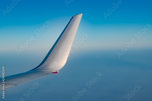 Winglet of Airplane from window, at high Altitude with crystal clear Blue Sky Wallpaper Mural