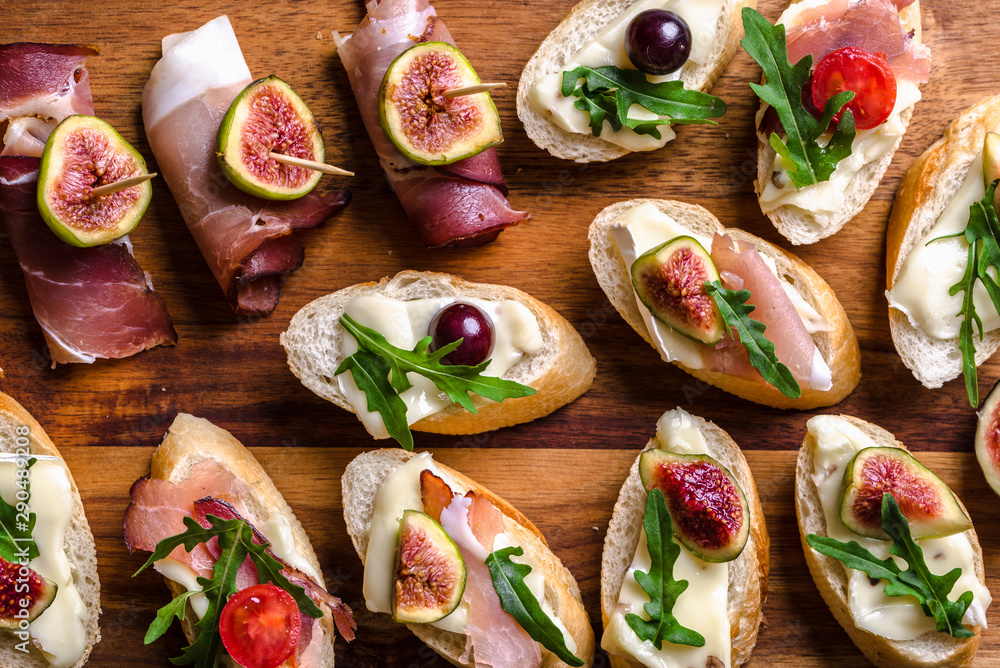 Fototapety, obrazy: Assorted brushetta - italian apetizer or traditional spanish tapas for sharing. Party food on catering platter. Antipasti with meat, cheese and fruits.