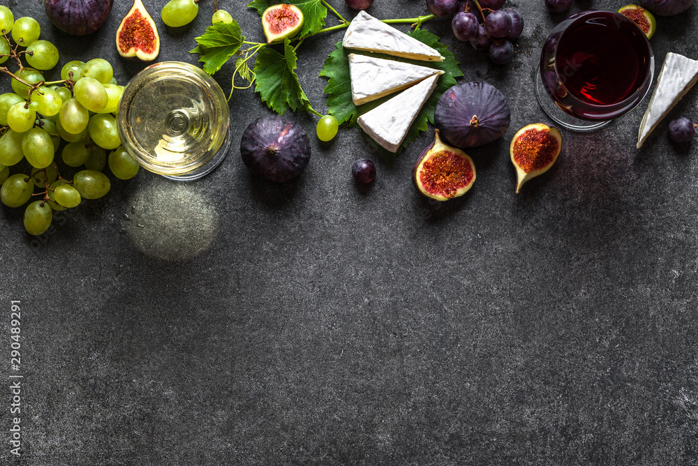 Fototapeta Glasses of red and white wine with cheese, grapes and figs
